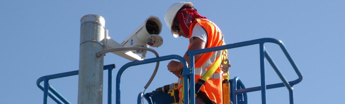 Technician installing perimeter surveillance camera