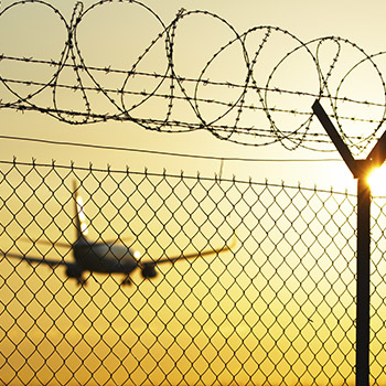 Airplane taking off in the distance with barbed wire fence in the foreground