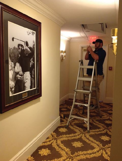 AISG field technition installing security cameras at Trump National Doral