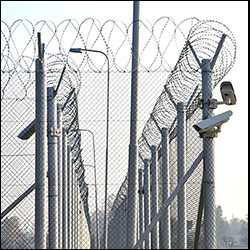 Double barrier secured perimeter fencing with barbed wire and cameras